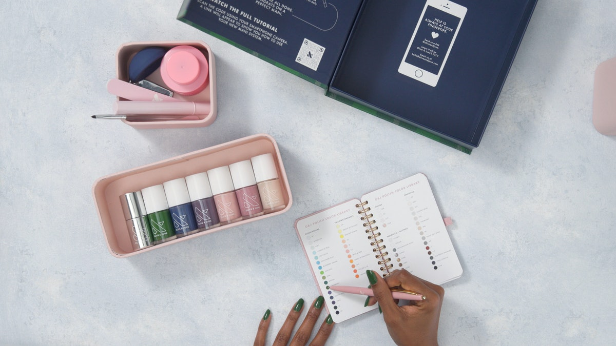 A model writes in a manicure notebook from Olive & June's Fall 2021 Mani System