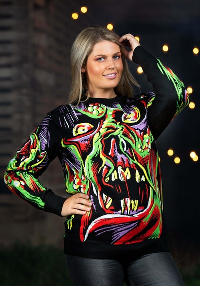 Woman posing in multi-colored sweater featuring abstract monster face