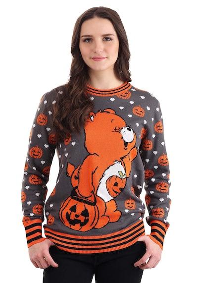 Woman wearing sweater featuring orange Care Bear for Halloween