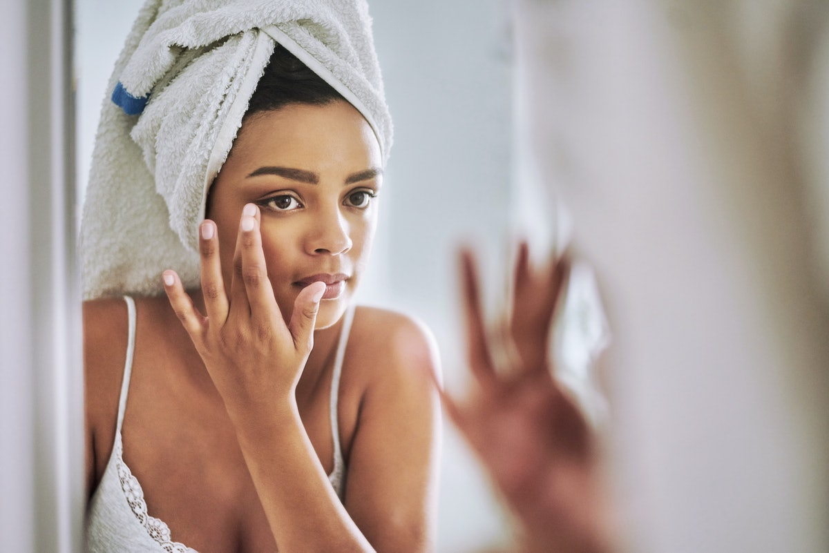 Woman touching face in mirror