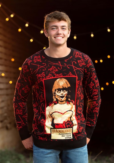 Man in sweater featuring Annabelle doll