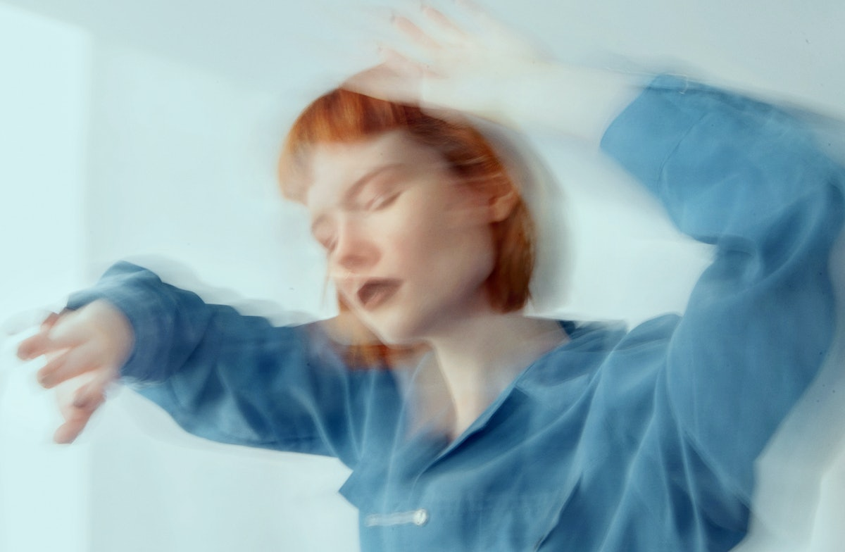 Red haired woman in blue shirt dancing, blurred motion during the blue moon on Aug. 22, 2021.
