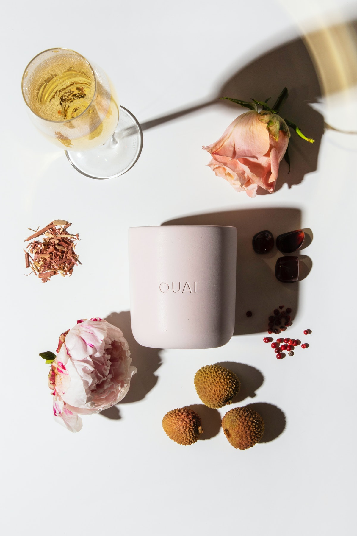 Ouai candle in Melrose Place surrounded by ingredients flat lay