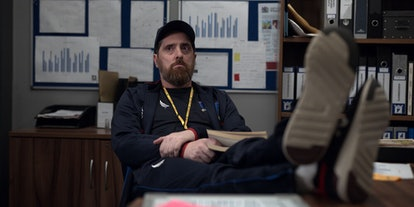 Coach Beard (Brendan Hunt) whose zodiac sign is Gemini, propping his feet up on his desk in the Appl...