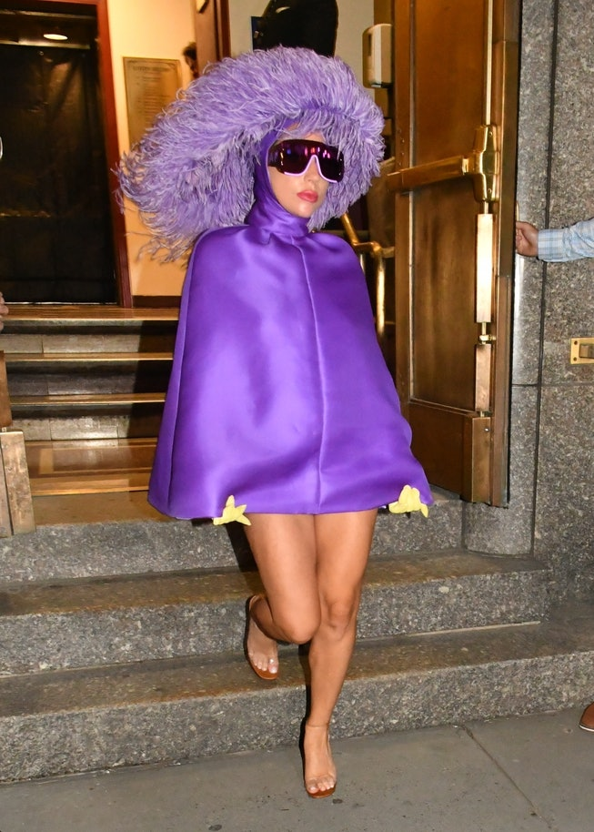 Lady Gaga wears a purple dress and matching headdress for her departure from Radio City Music Hall i...