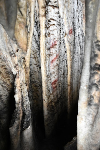 Close-up view of one of the curtains with red markings in Cueva de Ardales.