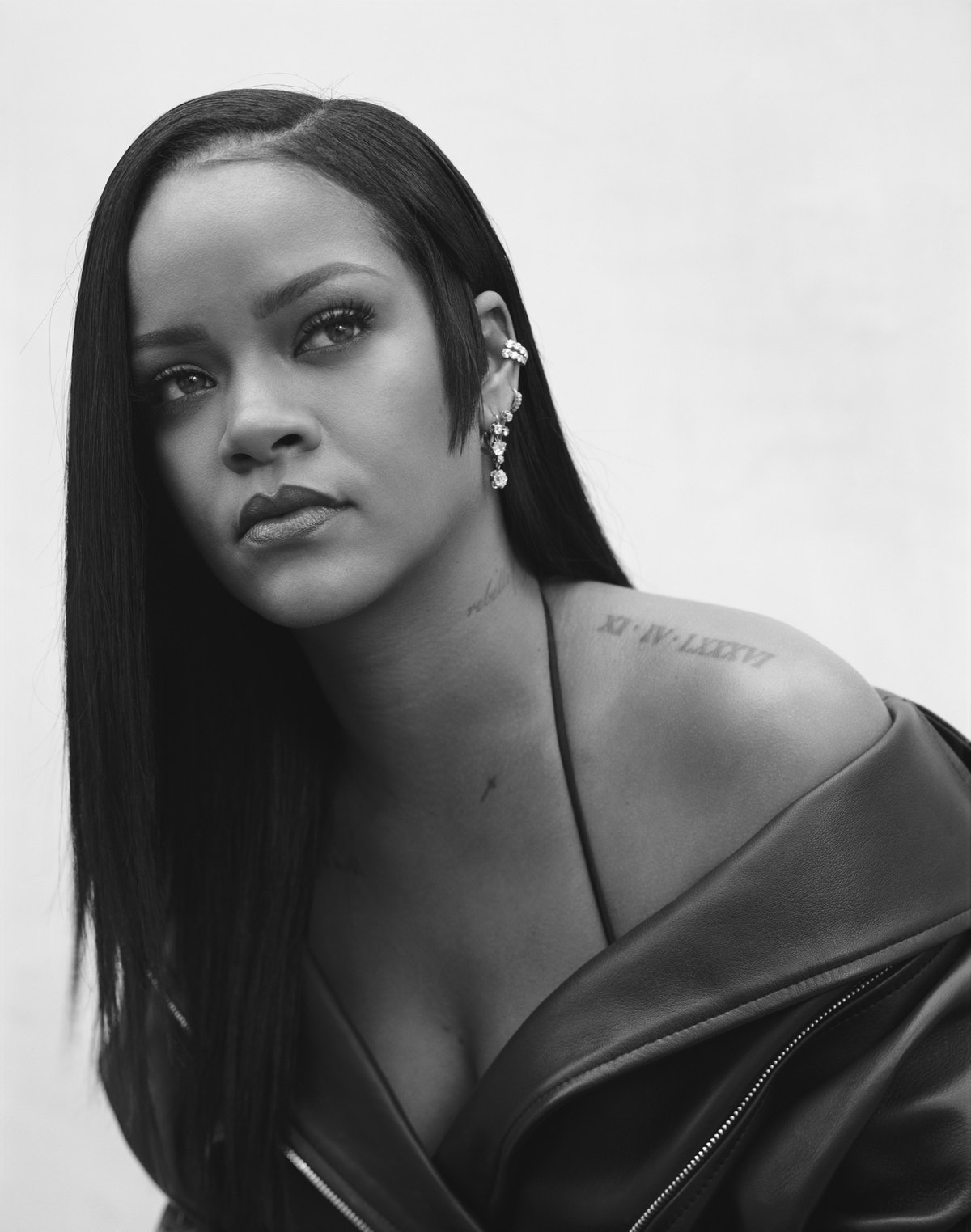 A promotional, black-and-white portrait of Rihanna with an asymmetrical side burn haircut for Fenty ...