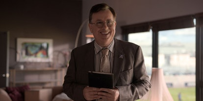 Leslie Higgins (Jeremy Swift) whose zodiac sign is Cancer, smiling at the camera in an office on the...