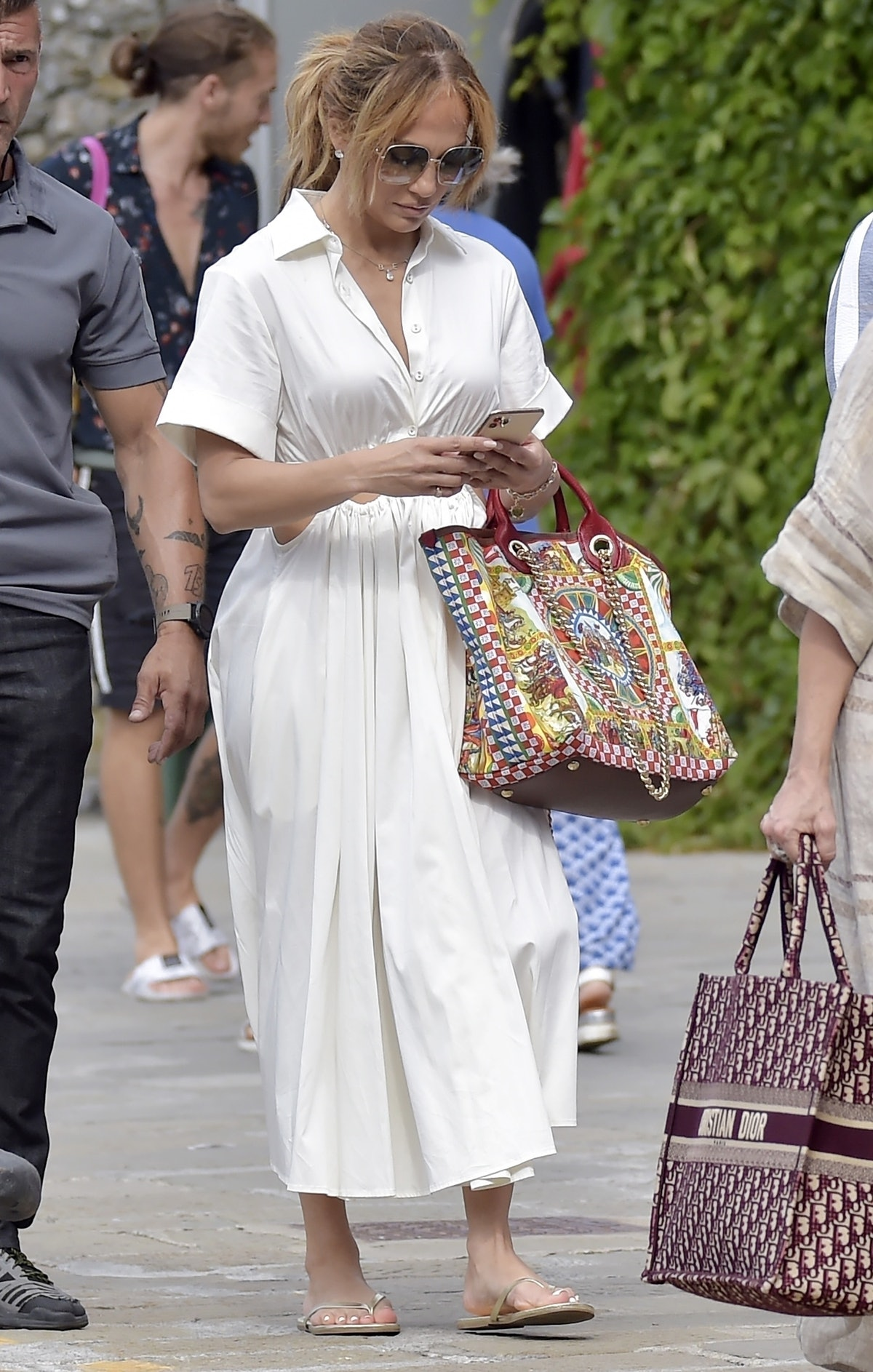 Jennifer Lopez wearing a white dress, gold flip-flops, and carrying a printed, embroidered tote bag.