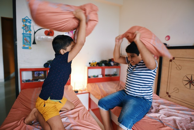 brothers having a pillow fight in their bedroom