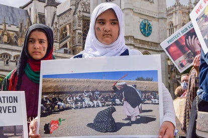 A young girl holds a picture of a woman being publicly beaten, during the demonstration in Parliamen...