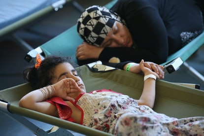A mother and daughter clutch hands as they sleep on cots at a registration center for migrants at a ...