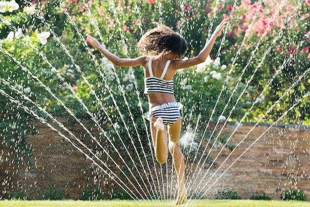 kid running through sprinklers