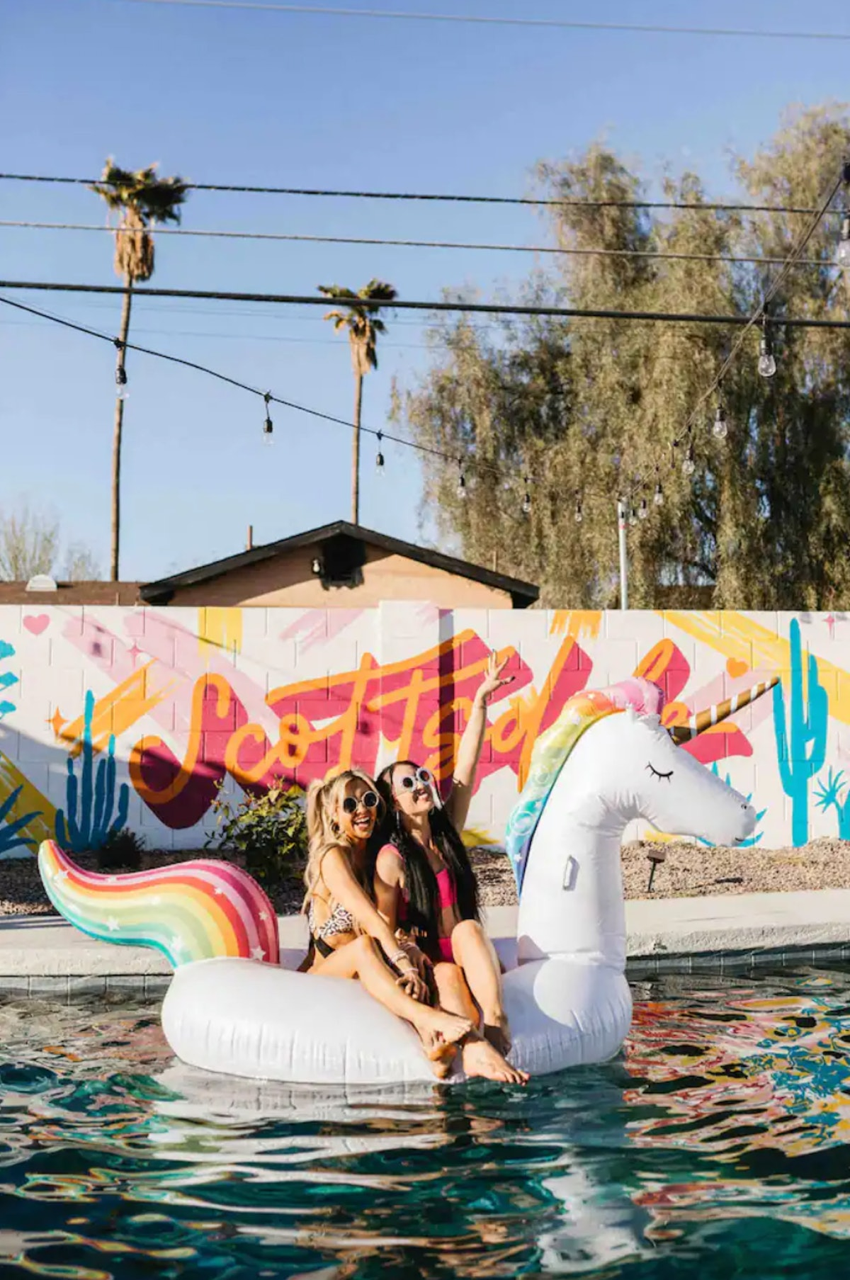 Friends sit on a pool float in the backyard of a 'Love Island'-themed Airbnb in Arizona.