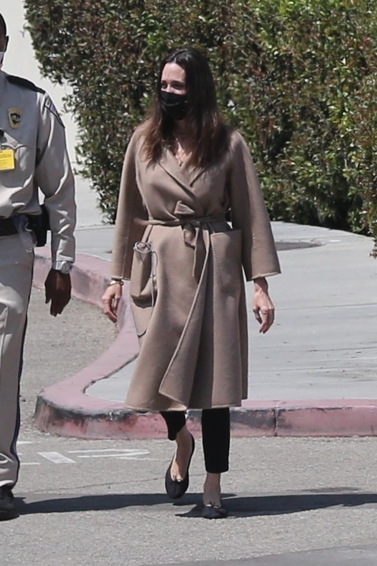 Angelina Jolie in a brown belted coat, black trousers, and black Chanel ballet flats.