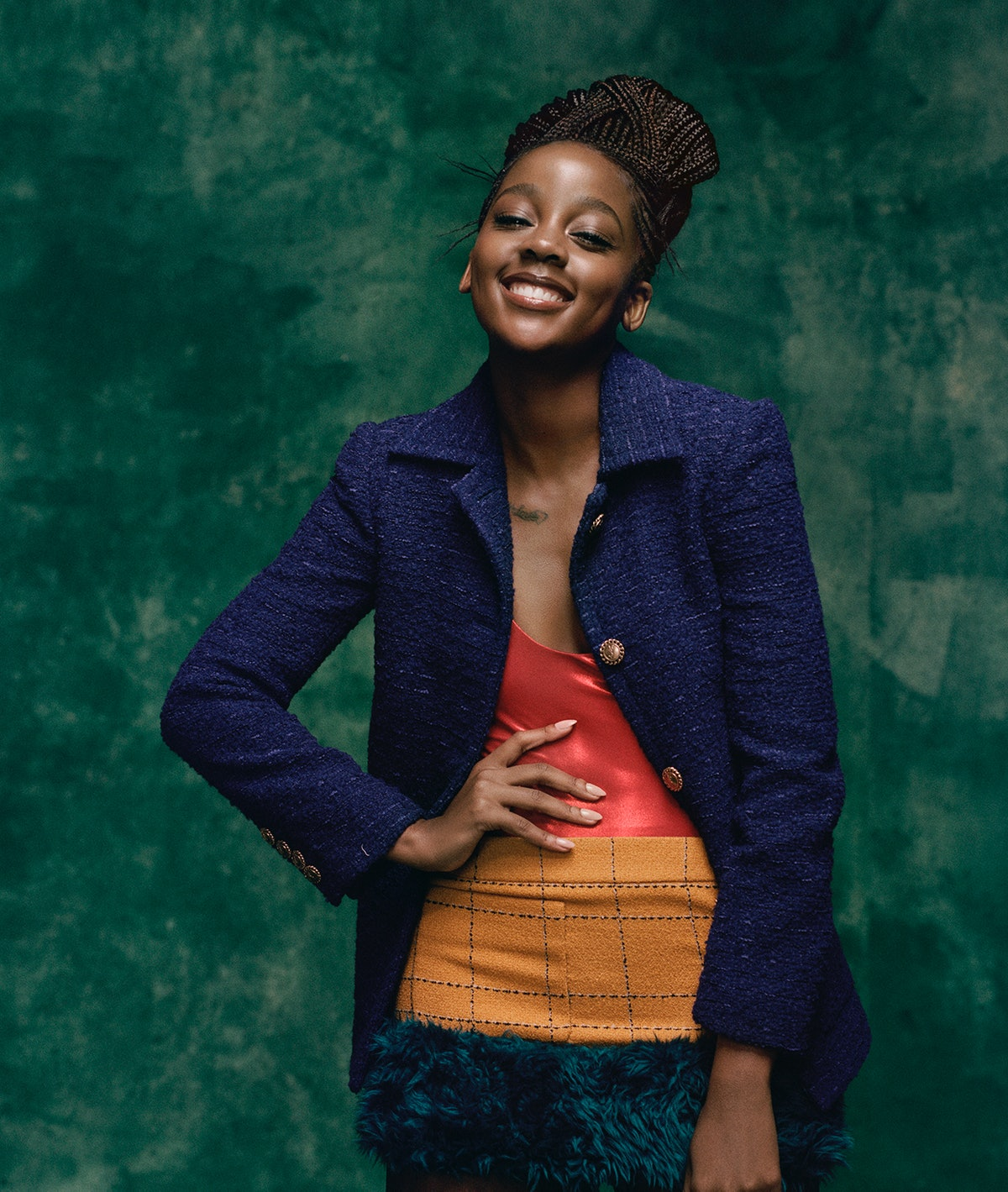 Thuso Mbedu wears a Saint Laurent by Anthony Vaccarello jacket, bodysuit, and miniskirt.