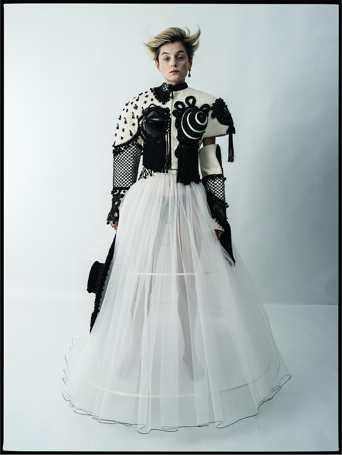 Emma Corrin wears a Schiaparelli Haute Couture jacket, skirt, and hat; Cartier earring.