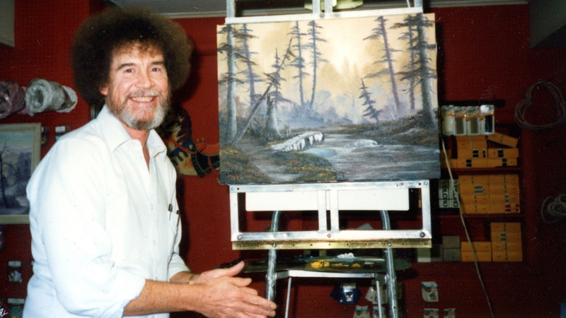Painter Bob Ross, sitting in front of one of his paintings, partnered with Annette and Walt Kowalski...