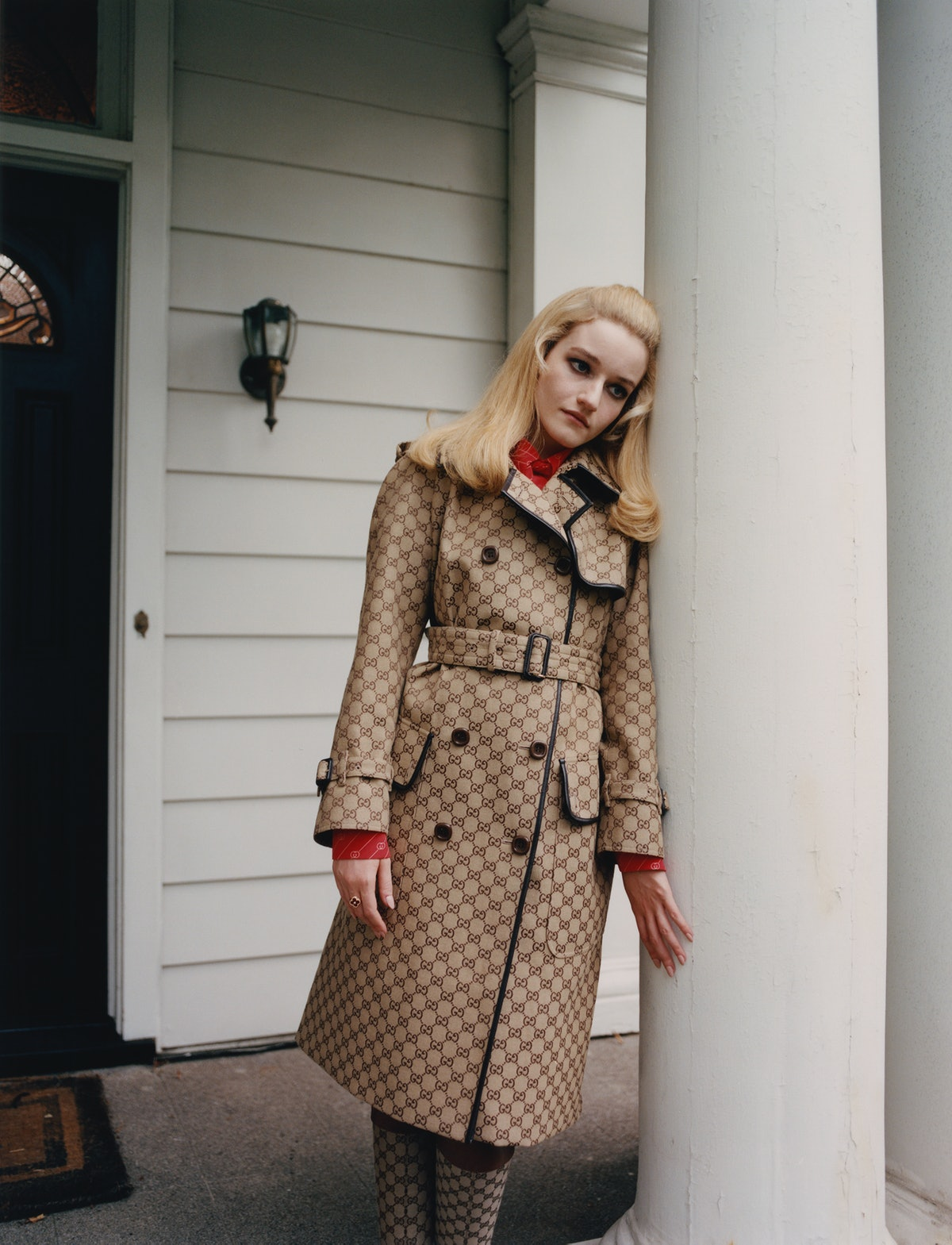 Julia Garner wears a Gucci coat, top, and boots; Van Cleef & Arpels ring.