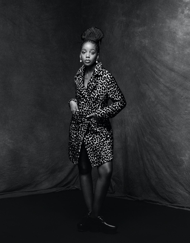 Thuso Mbedu wears a Dior coat; Prounis earrings; Prada shoes.