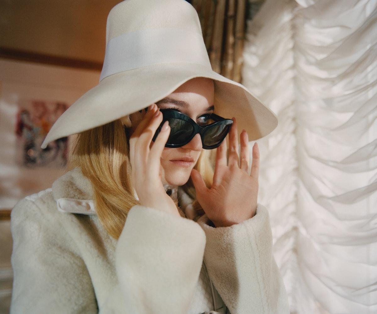 Julia Garner wears a Hermès coat; Albertus Swanepoel hat; Oliver Peoples sunglasses; Van Cleef & Arp...
