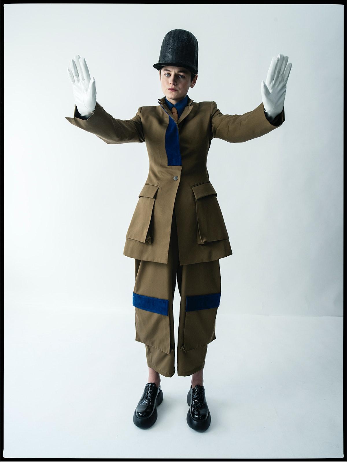 Emma Corrin wears a Loewe jacket, shirt, pants, and tie; Jo Miller Studio hat; AGL shoes; stylist's ...