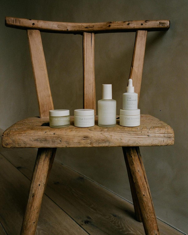 Oak Essentials skin care line arranged on wooden chair
