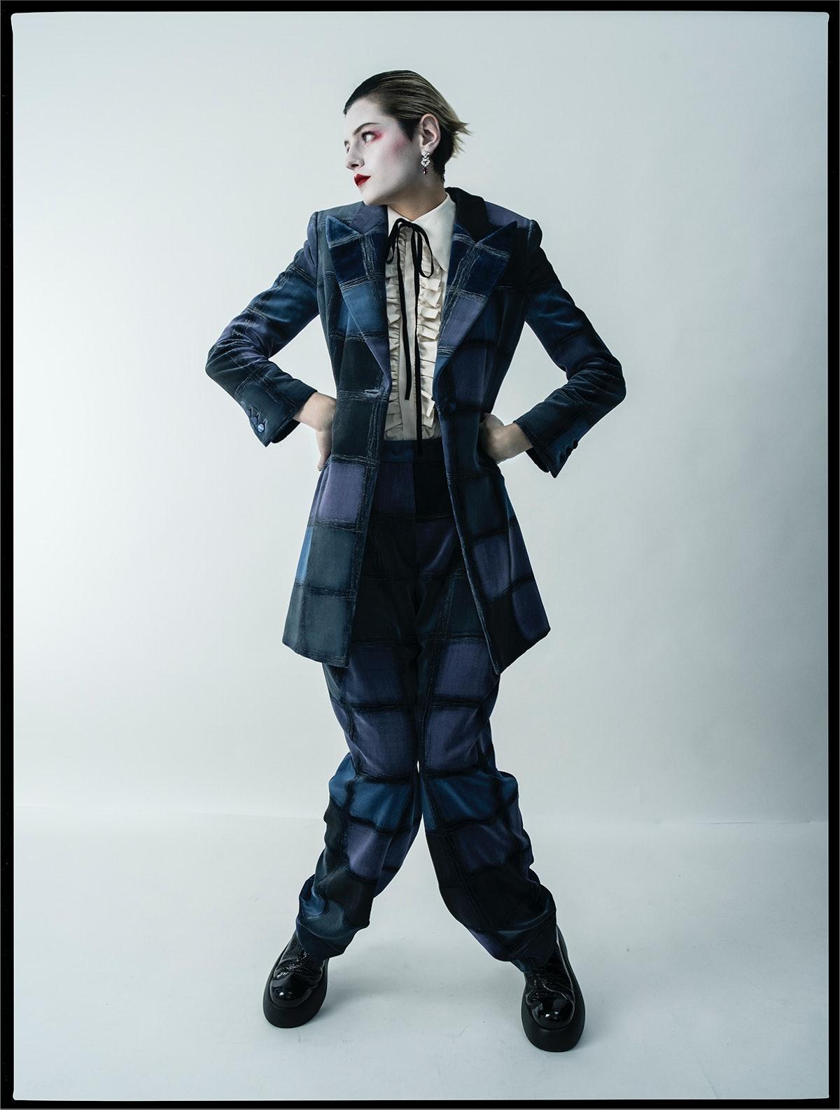 Emma Corrin wears a Giorgio Armani jacket and pants; Molly Goddard shirt; Cartier earrings; AGL shoe...