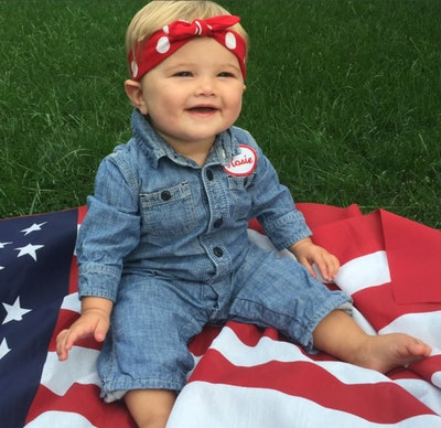 Baby girl sitting on American flag, dressed up as Rosie the Riveter