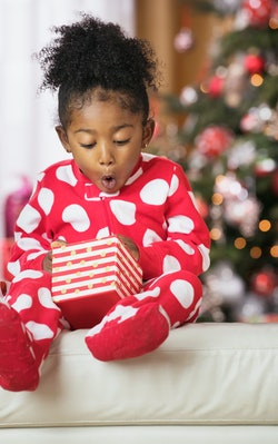 surprised and excited young girl in red and while polka dot pajamas opening christmas present