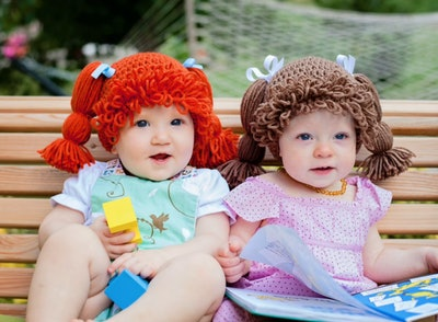 Two babies sitting next to each other wearing wigs that look like Cabbage Patch kids hair