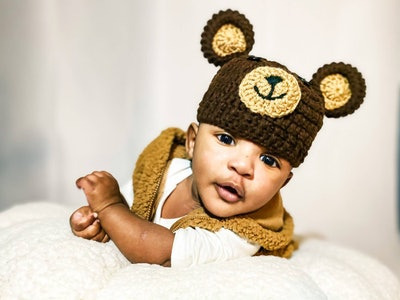 Baby laying on its tummy wearing beanie that looks like teddy bear with ears