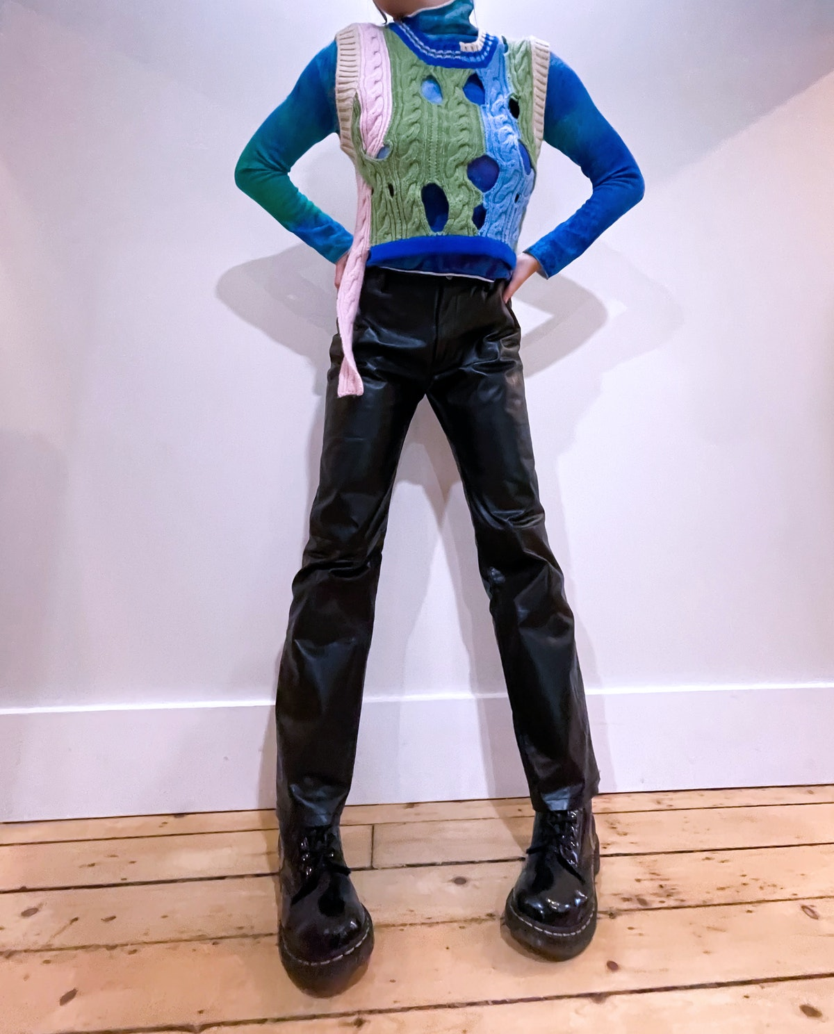 Emma Childs wears a blue turtleneck and multi-colored, cutout vest.