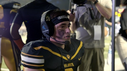 Jake Garcia getting coached via headset during a football game on 'Titletown High'.