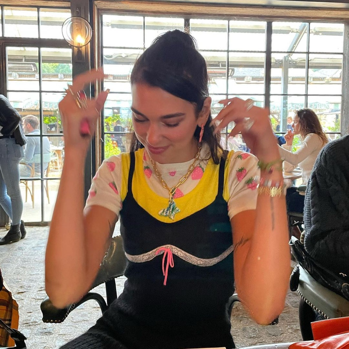 Dua Lipa wearing Mayol's Jenna Necklace with a graphic tee and a black slip dress.