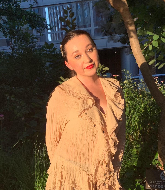 Emma Childs wears a tan, ruffled blouse.