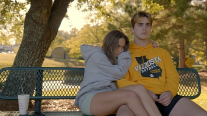 Grayson Leavy and Zoey Watson cuddling on a park bench on 'Titletown High'.