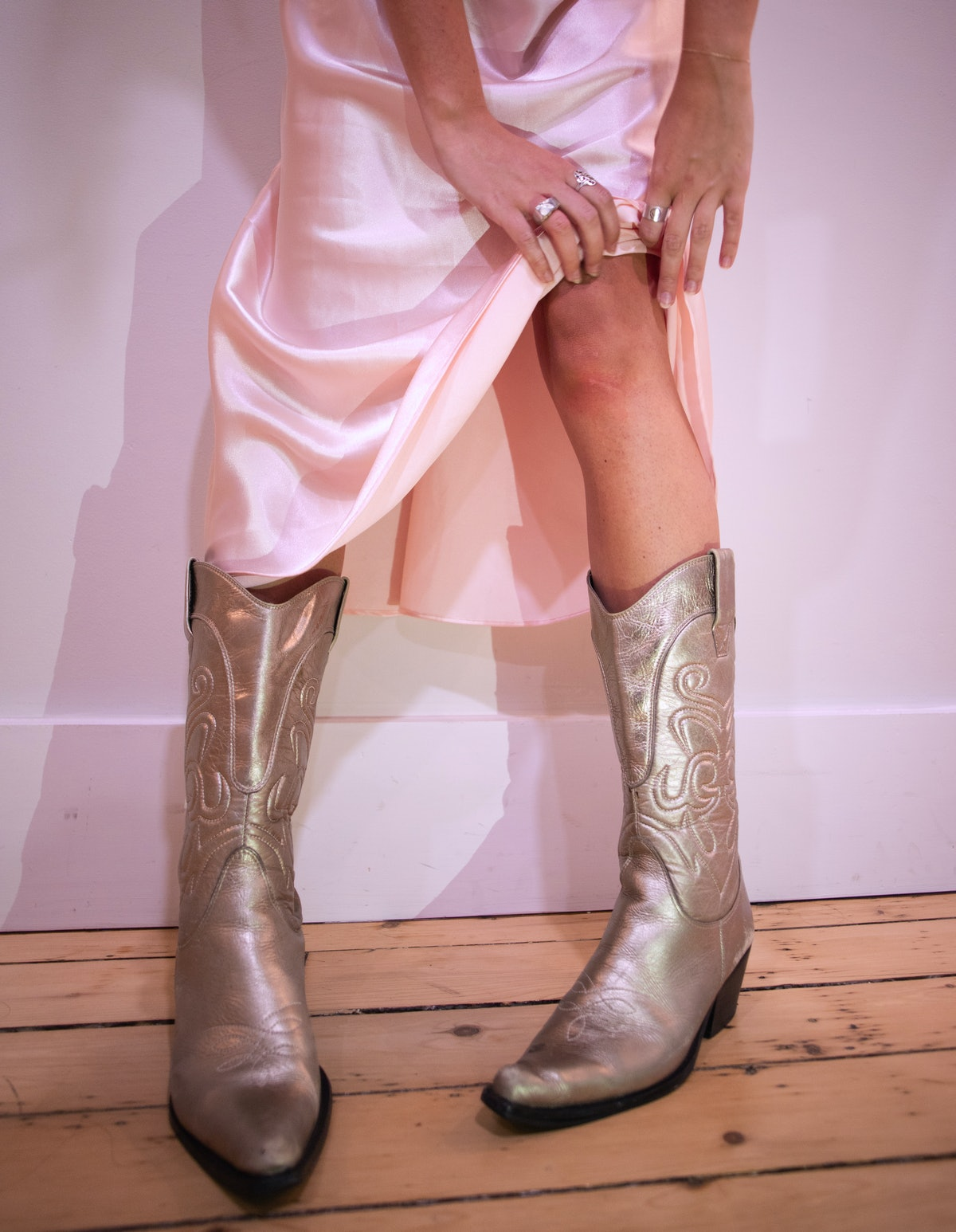 Emma Childs wearing a pink slip dress in silver cowboy boots.