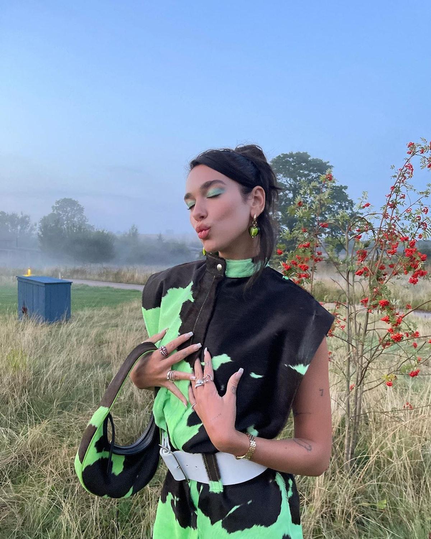 Dua Lipa wears Mayol Jewelry's Heart of Glass Earings and a  neon green cow print two-piece set.