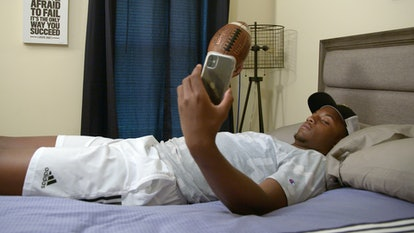 Amari Jones playing with a football in bed while on the phone on 'Titletown High'.
