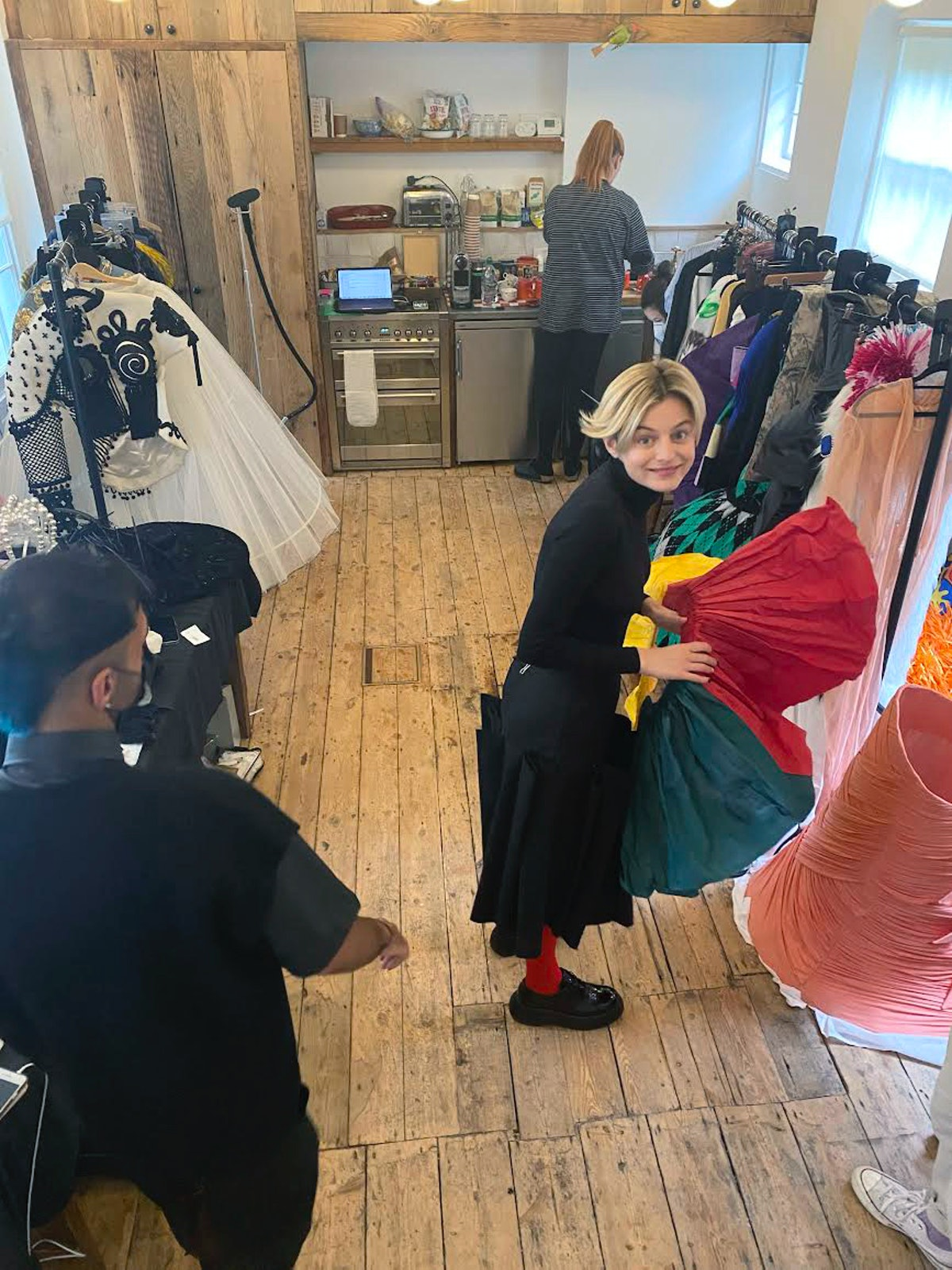 Emma Corrin pulling a skirt from a rack at photographer Tim Walker's studio.
