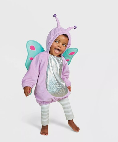 Baby/toddler girl standing, making a funny face, dressed in butterfly costume