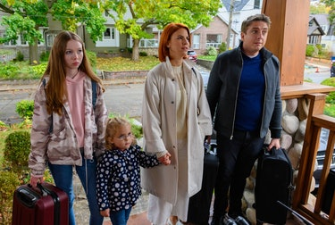 The Carlsons standing on a front porch, holding hands with suitcases