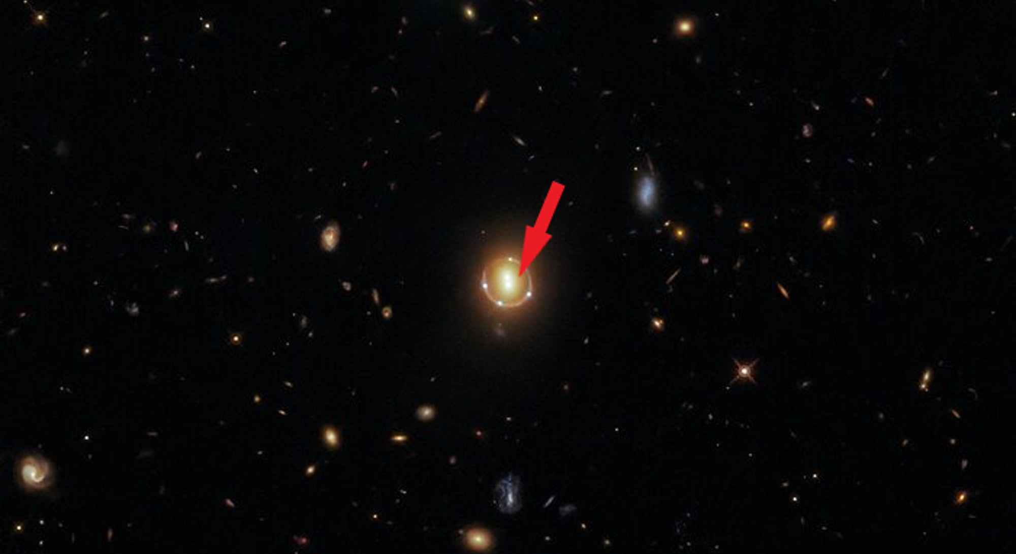 A Hubble image of the cluster, characterized by two bright spots in the center and four small light ...