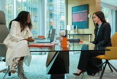 Sloane Mitchell (Enuka Okuma) and Kate Foster (Catherine Reitman) sit across from each other at a de...