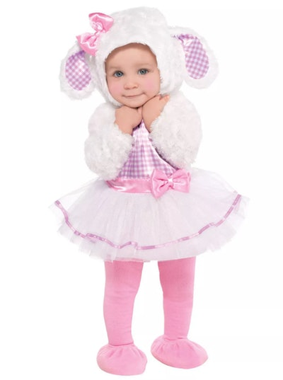 Baby girl standing, smiling, wearing a lamb costume