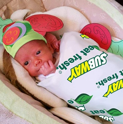 Infant swaddled in blanket to look like a subway foot-long sandwich