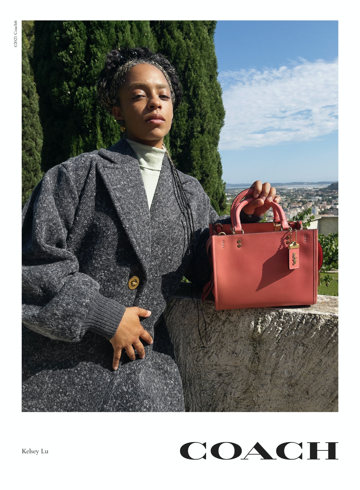 Kelsey Lu stars in Coach's Rogue bag campaign, posing next to red Rogue 25 handbag in Colorblock.