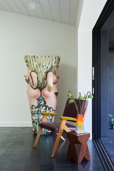 Flanking a José Zanine Caldas armchair  are Ruby Neri's sculpture Untitled (Tall Double Lady), 2016,...