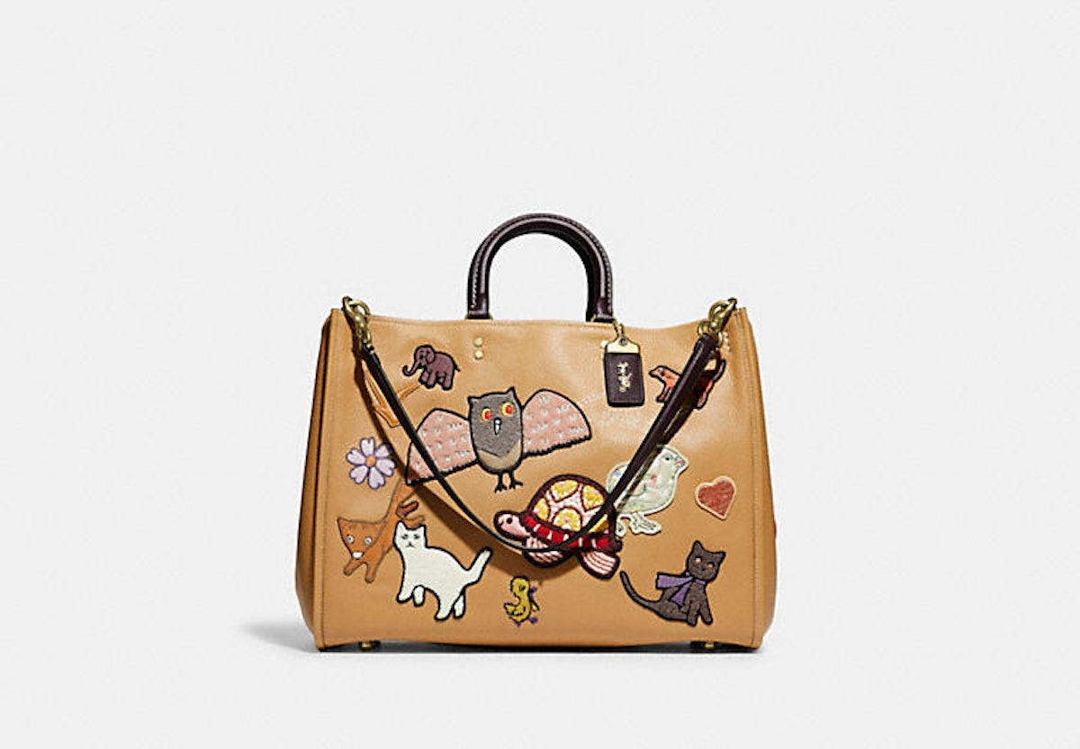 Coach Rogue 39 bag in tan leather with creature patches.